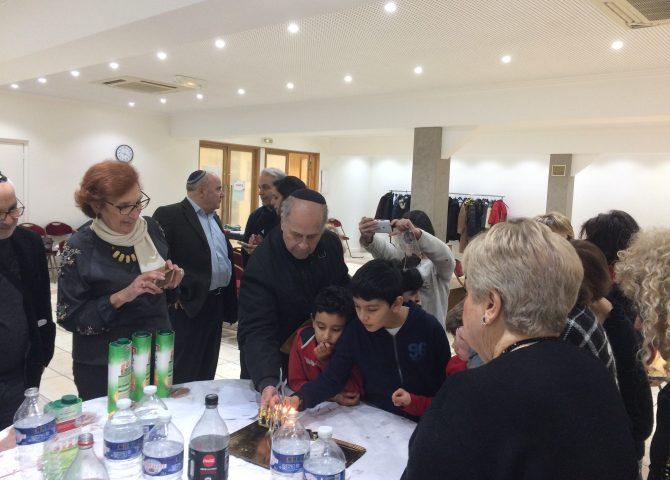 deux enfants et un groupe de personnes qui allument des bougies