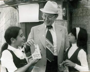 Une personne agée et deux petites filles avec une boîte bleue du KKL