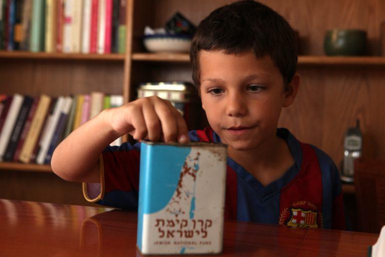 Un enfant qui place une pièce dans une boîte bleue